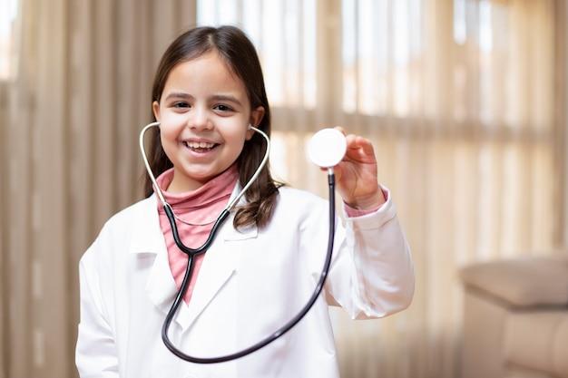 Portret van glimlachend klein kind kleedde zich als arts met een stethoscoop in haar hand