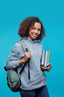 Portret van glimlachend krullend afro-amerikaans studentenmeisje dat zich met boeken en tas tegen blauwe achtergrond bevindt