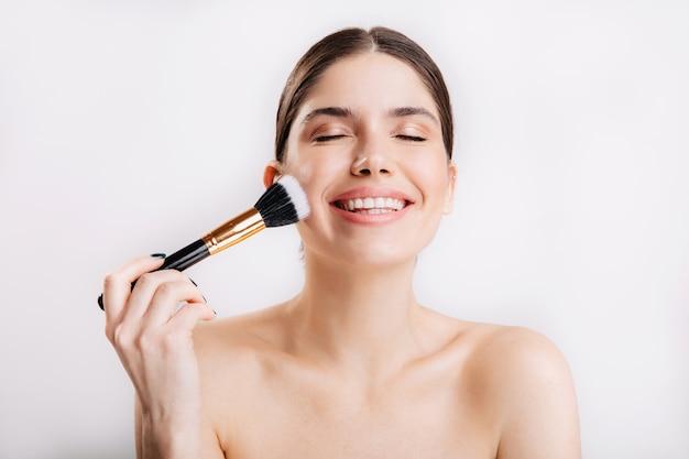Portret van glimlachend meisje dat met schone huid poederborstel op gezicht toepast tegen geïsoleerde muur.