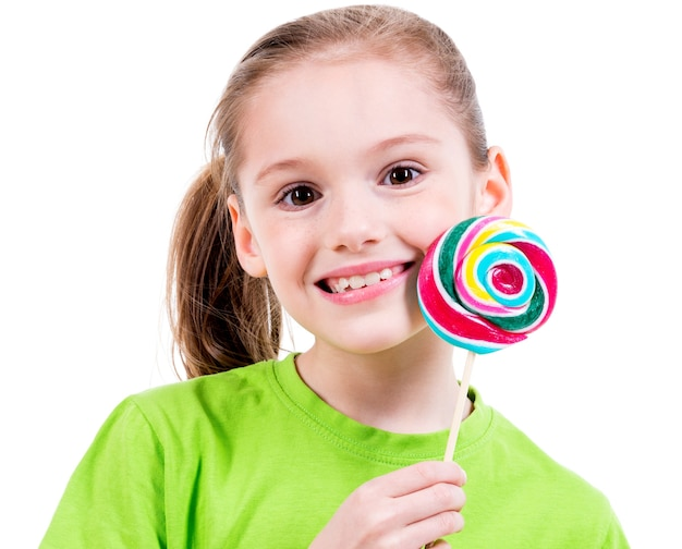 Portret van glimlachend meisje in groen t-shirt met gekleurd suikergoed - dat op wit wordt geïsoleerd.