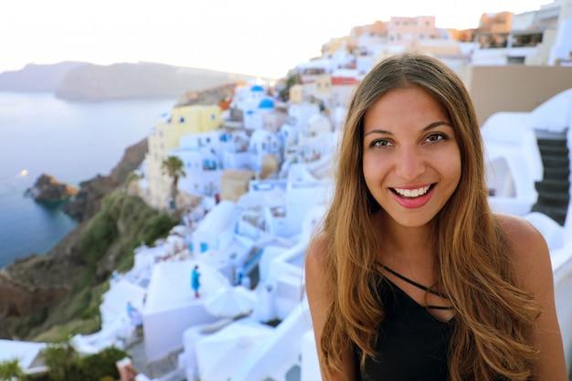 Portret van glimlachend meisje in het dorp van oia, santorini. leuk gelukkig toeristenmeisje dat foto neemt tijdens de zomervakantie in de beroemde europese bestemming santorini, griekenland.
