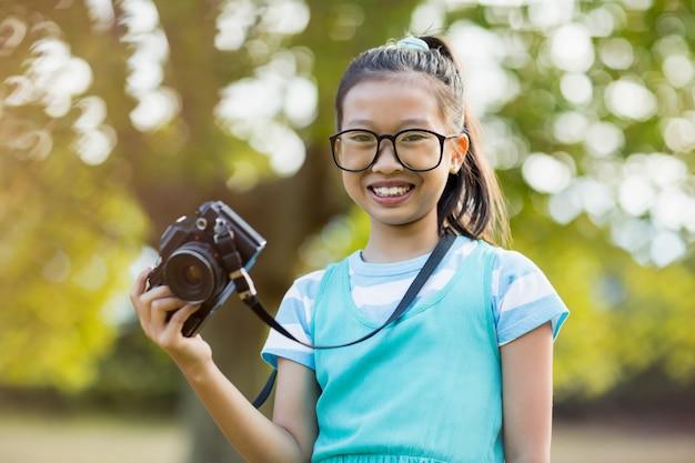 Portret van glimlachend meisje in schouwspel dat een camera houdt