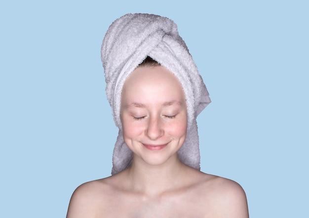 Portret van glimlachend meisje met gesloten ogen met handdoek op hoofd zonder make-up die op blauwe achtergrond wordt geïsoleerd