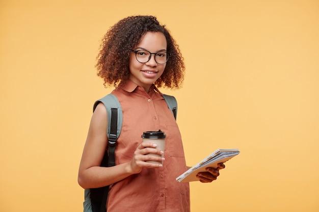 Portret van glimlachend mooi afrikaans-amerikaans studentenmeisje in brillen die koffie drinken terwijl het oplossen van taak tegen gele achtergrond
