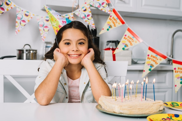 Portret van glimlachend mooi meisje met verjaardagscake op lijst