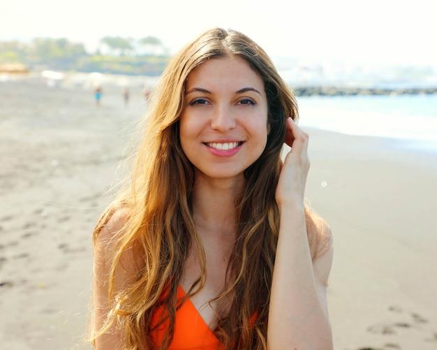 Portret van glimlachend mooi sensueel meisje in oranje bikini op het strand