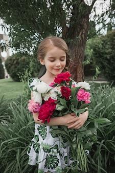 Portret van glimlachend mooi tienermeisje met boeket van pioenrozen tegen groen gras bij zomerpark. kindermode concept.