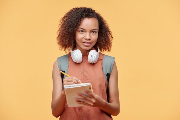 Portret van glimlachend nieuwsgierig afro-amerikaans studentenmeisje met krullend haar die draadloze hoofdtelefoons dragen die aantekeningen maken in kladblok tegen gele achtergrond