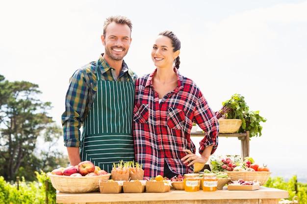Portret van glimlachend paar die organische groenten verkopen