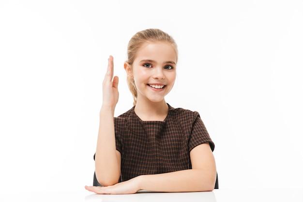 Portret van glimlachend schoolmeisje dat aan het bureau zit op les terwijl ze vakken studeert op school geïsoleerd over een witte muur