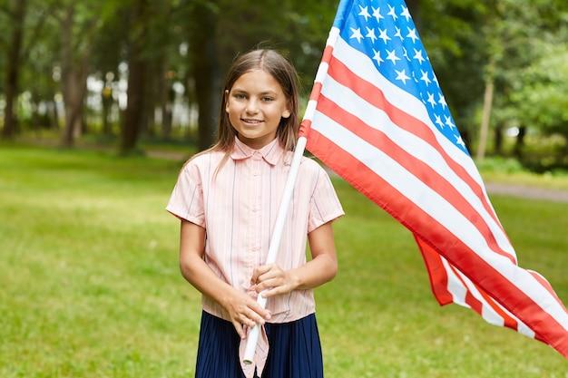Portret van glimlachend schoolmeisje dat amerikaanse vlag draagt terwijl hij buiten in park staat
