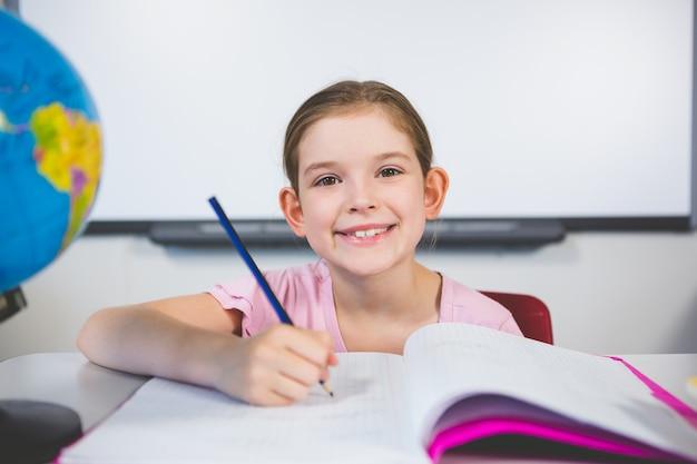 Portret van glimlachend schoolmeisje dat huiswerk in klaslokaal doet
