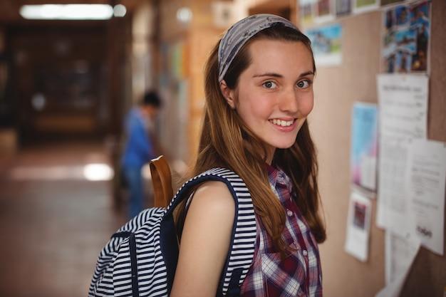 Portret van glimlachend schoolmeisje dat zich dichtbij mededelingenbord in gang bevindt