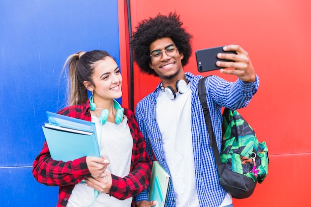Portret van glimlachend tienerpaar die selfie samen op cellphone tegen gekleurde muur nemen