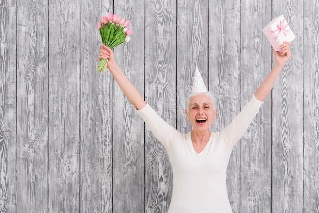 Portret van glimlachend verjaardag vrouw met bloemboeket met geschenkdoos voor houten achtergrond