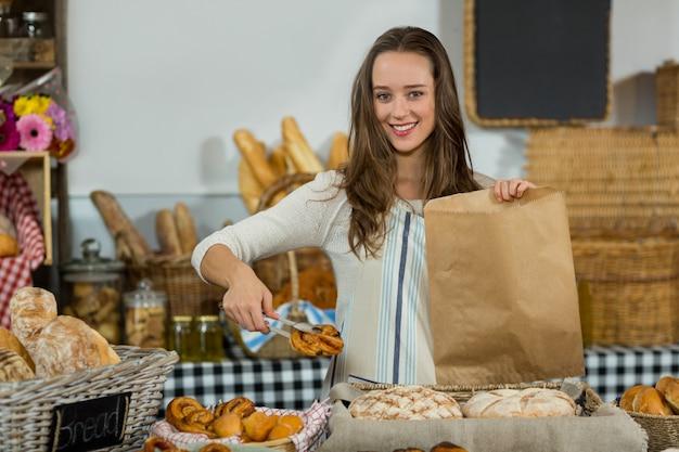 Portret van glimlachend vrouwelijk personeel die croissant zetten in een document zak bij teller