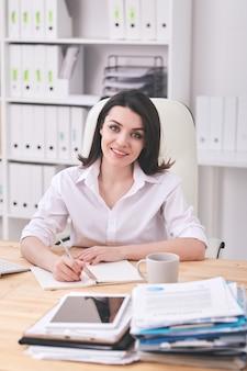 Portret van glimlachende aantrekkelijke jonge vrouw in wit overhemd aan bureau zitten en in bureau werken