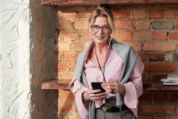 Portret van glimlachende aantrekkelijke rijpe dameondernemer in glazen die smartphone met behulp van