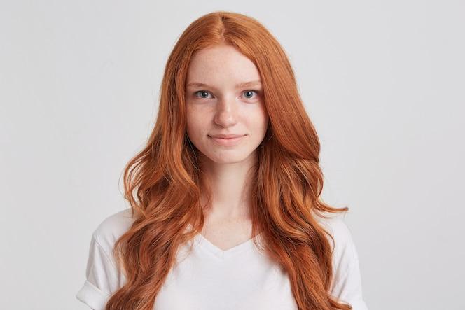 Portret van glimlachende aantrekkelijke roodharige jonge vrouw met lang golvend haar