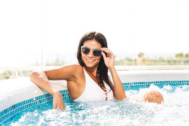 Portret van glimlachende aantrekkelijke vrouw in wit badpak en zonnebril zittend in zwembad, buiten in kuuroord