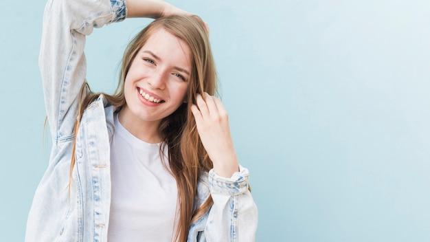 Portret van glimlachende aantrekkelijke vrouw op blauwe muur