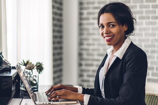 Portret van glimlachende afrikaanse amerikaanse vrouw die laptop met behulp van