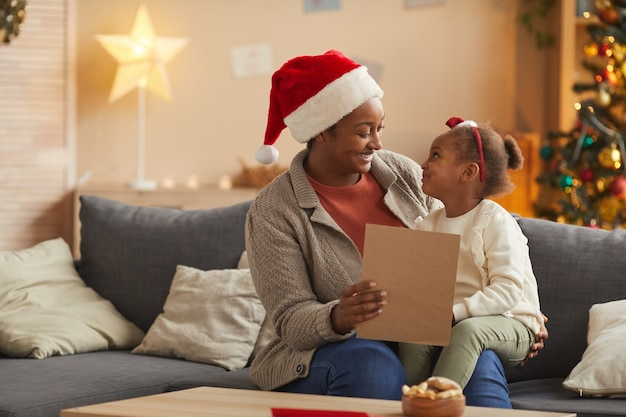Portret van glimlachende afro-amerikaanse moeder die de brief aan de kerstman leest met een schattig klein meisje terwijl u thuis geniet van het kerstseizoen, kopieer ruimte