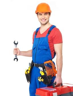 Portret van glimlachende arbeider met hulpmiddelen en moersleutel die op wit wordt geïsoleerd
