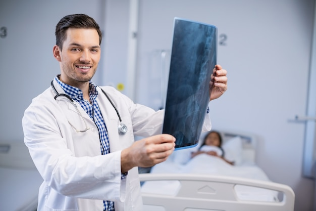 Portret van glimlachende arts die röntgenstraal van patiënt onderzoekt