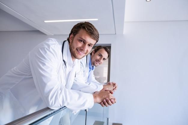 Portret van glimlachende artsen die op traliewerk in gang leunen