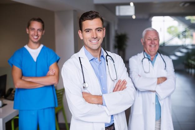 Portret van glimlachende artsen die zich met gekruiste wapens bevinden