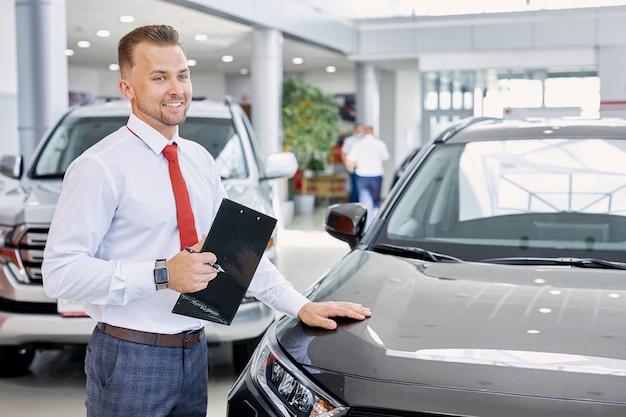 Portret van glimlachende autodealer op het werk