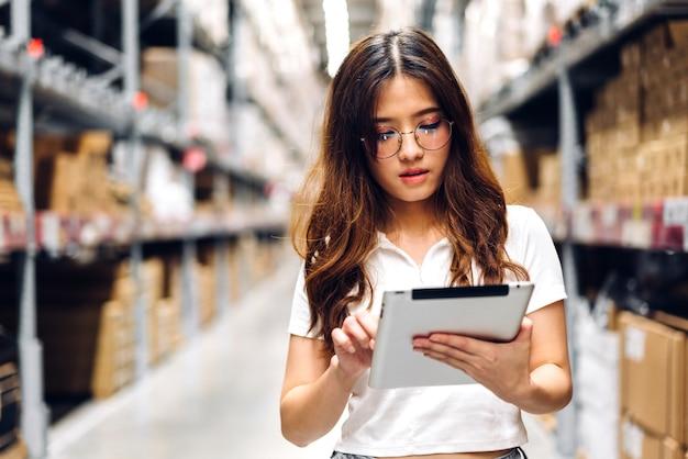 Portret van glimlachende aziatische ingenieur in de besteldetails van de helmenvrouw op tabletcomputer