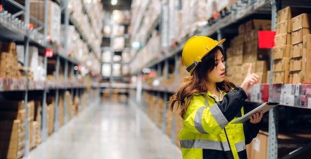 Portret van glimlachende aziatische ingenieur in de bestelgegevens van de helmenvrouw op tabletcomputer voor het controleren van goederen en leveringen op planken