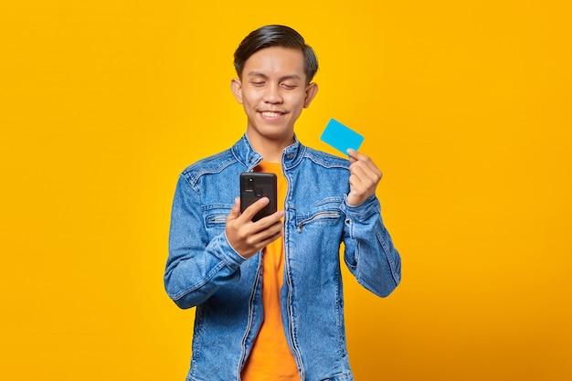 Portret van glimlachende aziatische man die creditcard gebruikt om met mobiele telefoon te betalen