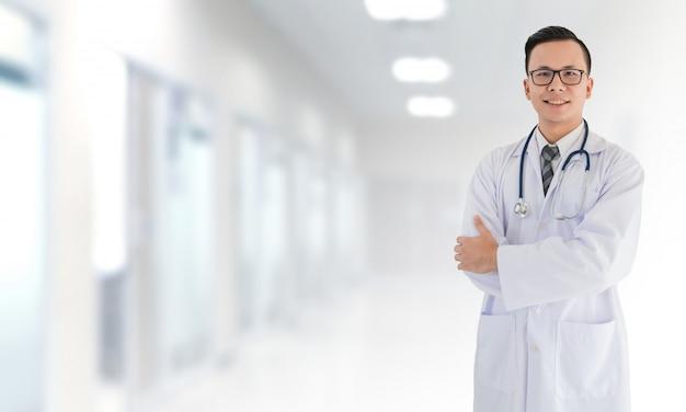 Portret van glimlachende aziatische medische mannelijke arts die zich voor het vage binnenlandse ziekenhuis bevindt