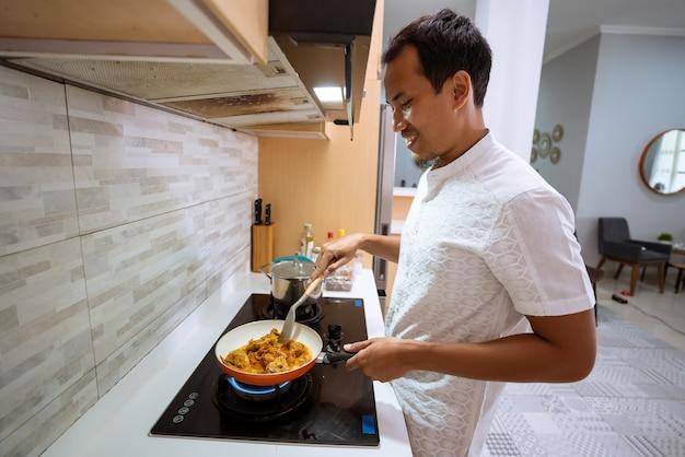Portret van glimlachende aziatische moslimman die kookt voor het iftar-diner op ramadan