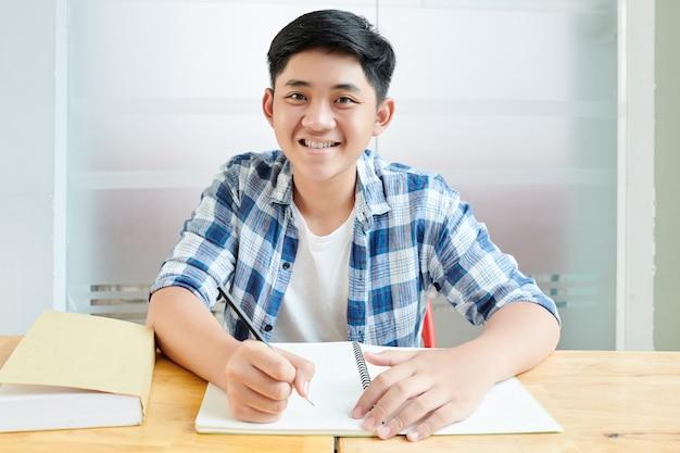 Portret van glimlachende aziatische schooljongen die en in voorbeeldenboek schrijven wanneer zij aan bureau zitten