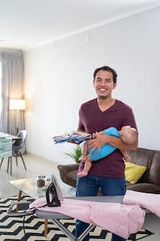 Portret van glimlachende aziatische vader die zijn kleren strijkt terwijl hij zijn baby op zijn hand houdt