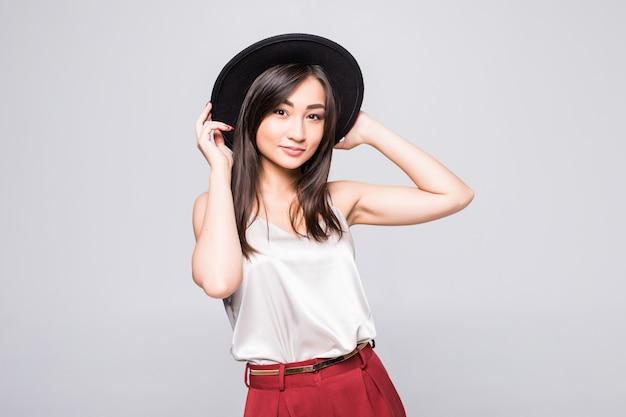 Portret van glimlachende aziatische vrouw met zwarte hoed die op witte muur wordt geïsoleerd