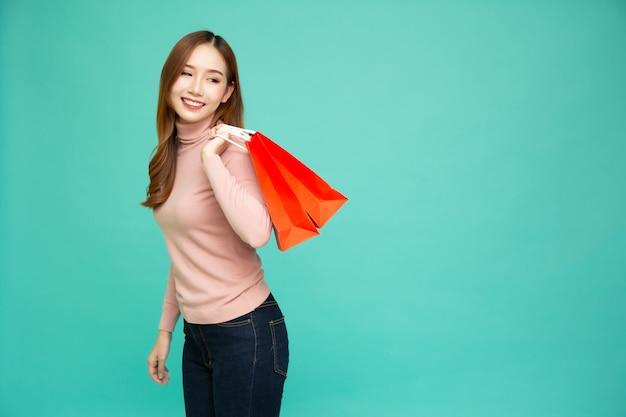 Portret van glimlachende aziatische vrouwen die holdings rode boodschappentas dragen die over groen wordt geïsoleerd.