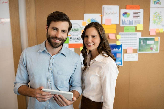 Portret van glimlachende bedrijfscollega's die aan digitale tablet werken