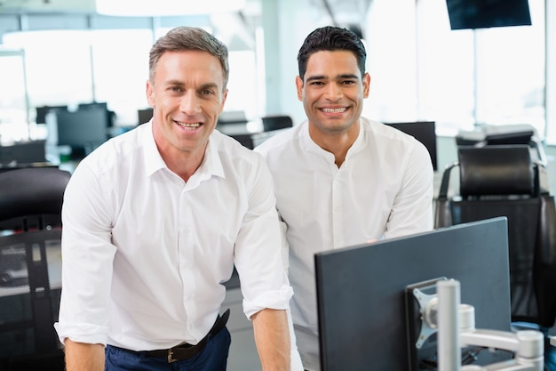 Portret van glimlachende bedrijfscollega's die bij bureau werken