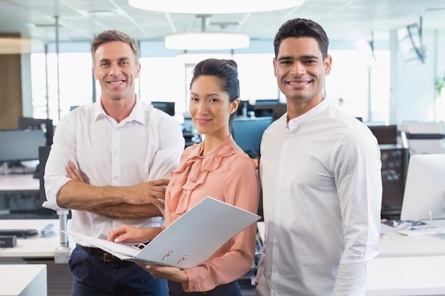 Portret van glimlachende bedrijfscollega's die zich met klembord bij bureau bevinden