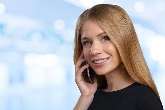 Portret van glimlachende bedrijfsvrouw die de telefoon spreekt