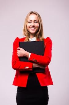 Portret van glimlachende bedrijfsvrouw met rode omslag, die op witte muur wordt geïsoleerd