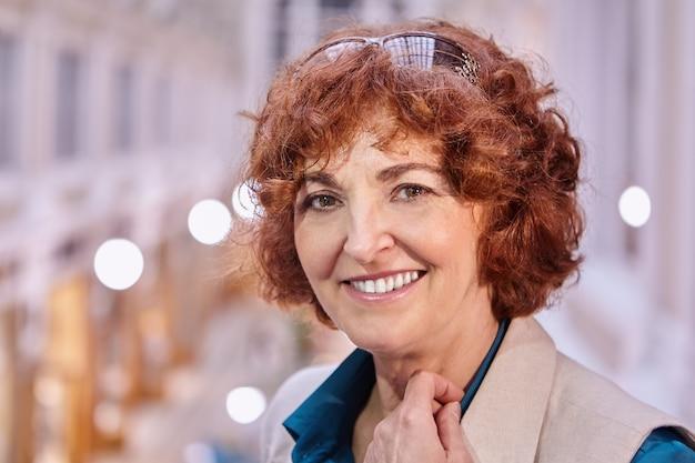 Portret van glimlachende blanke vrouw van middelbare leeftijd met rood kort krullend haar en zonnebril.