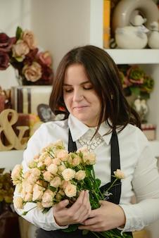 Portret van glimlachende bloemist die op roomrozen kijkt die de bloemen in de winkel verpakken