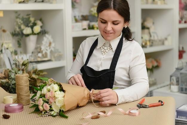 Portret van glimlachende bloemist die zich dichtbij de lijst bevindt die de bloemen in de winkel inpakt