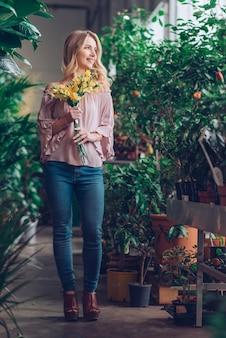 Portret van glimlachende blonde jonge vrouw die gele bloem houdt